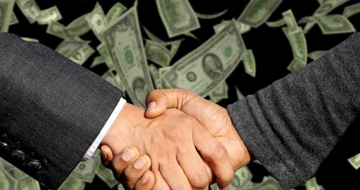 big pharma and politicians paid off, handshake with money